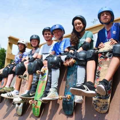 Group of campers with skateboards and helmets