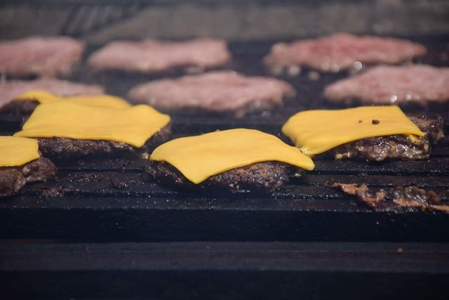 cheeseburgers cooking on grill