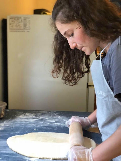 girl rolling out dough for pizza