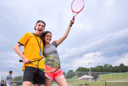 Two campers with tennis rackets on the tennis court