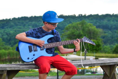 Boy camper playing the electric guitar outside