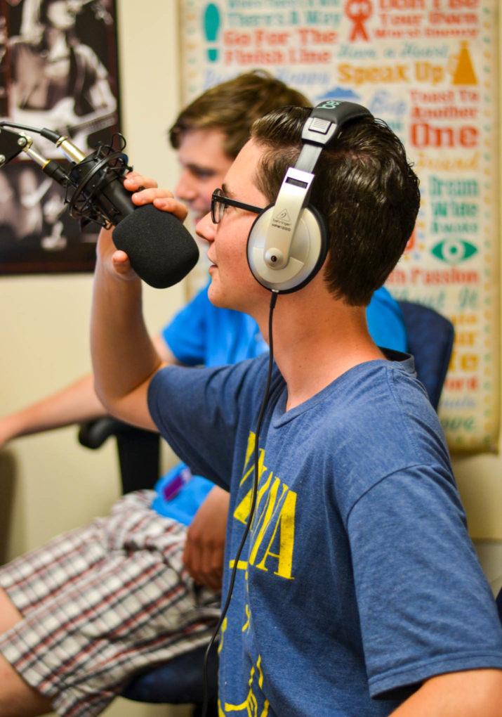 Camper speaking into a microphone in a radio studio