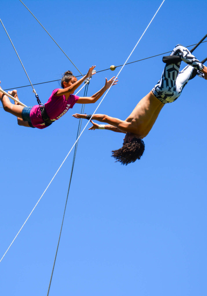 Instructor catching camper doing a trapeze stunt