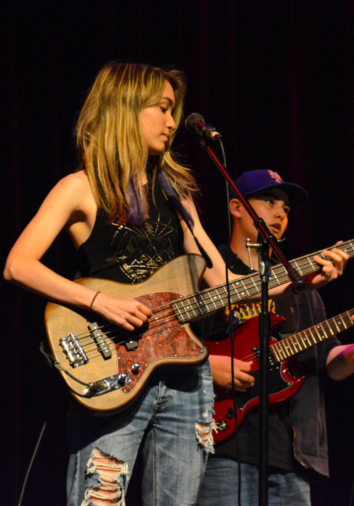 Girl camper playing the guitar on stage in a band