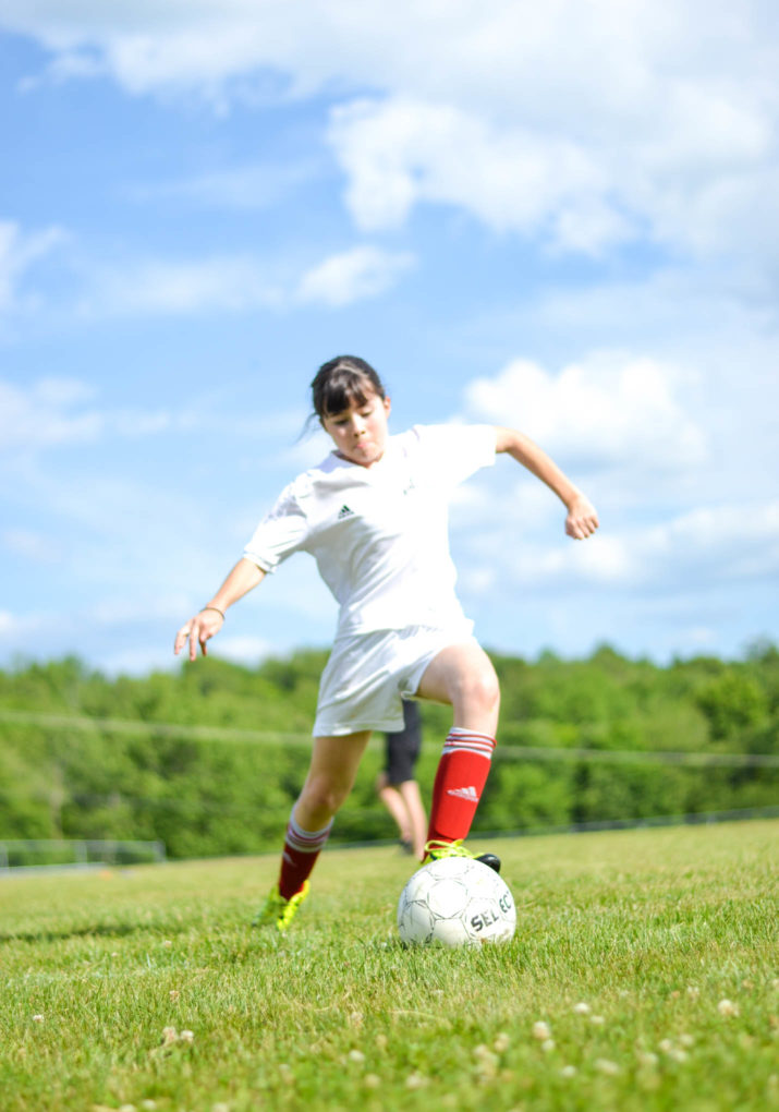 Camper about to kick a soccer ball