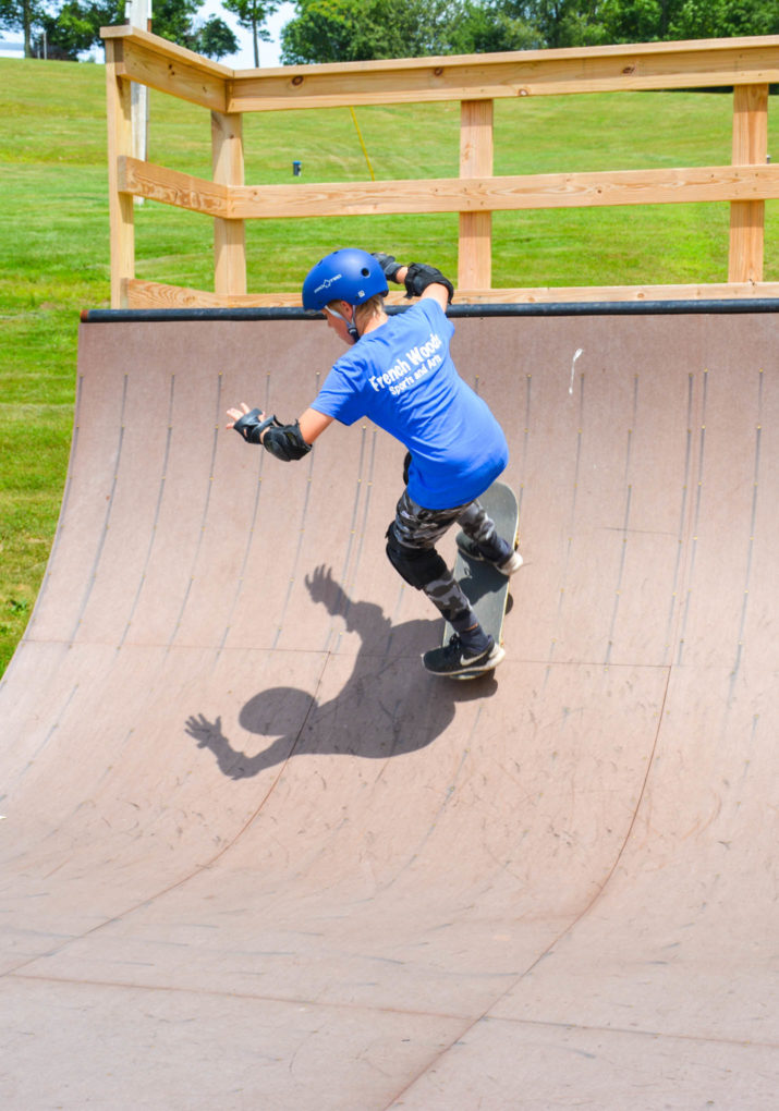 Camper riding down the half pipe on a skateboard
