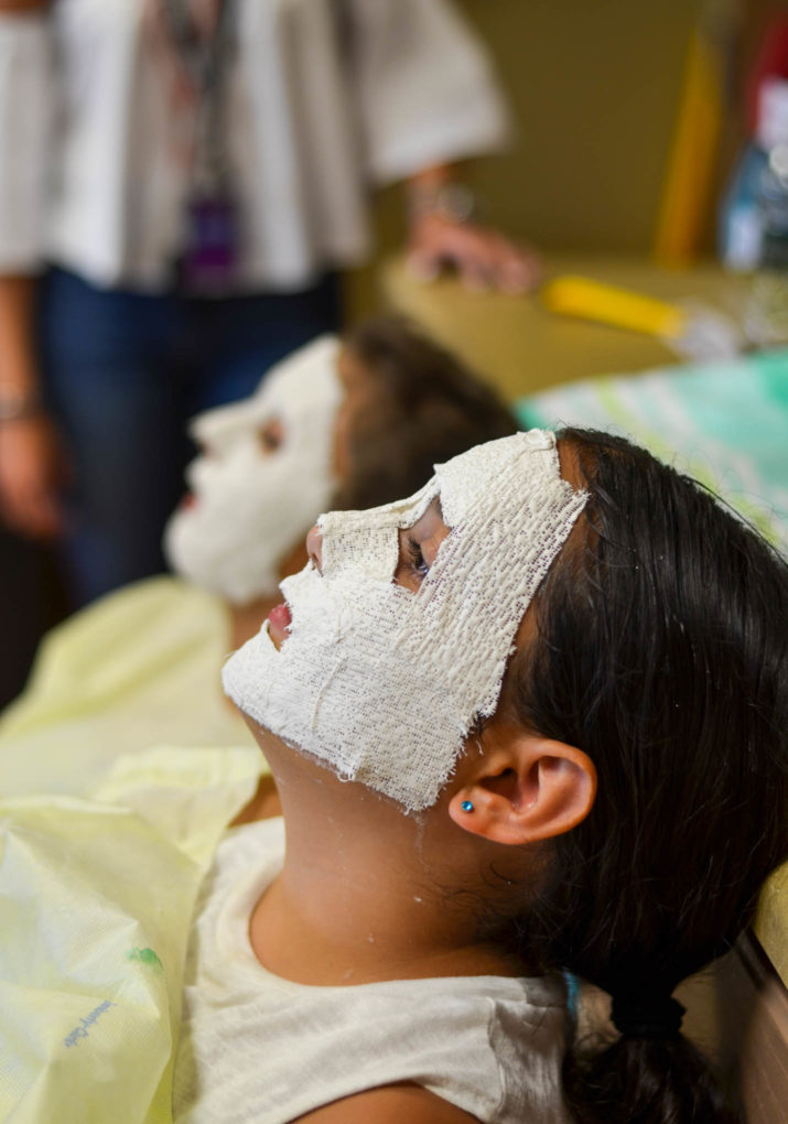 Campers molding their faces for masks