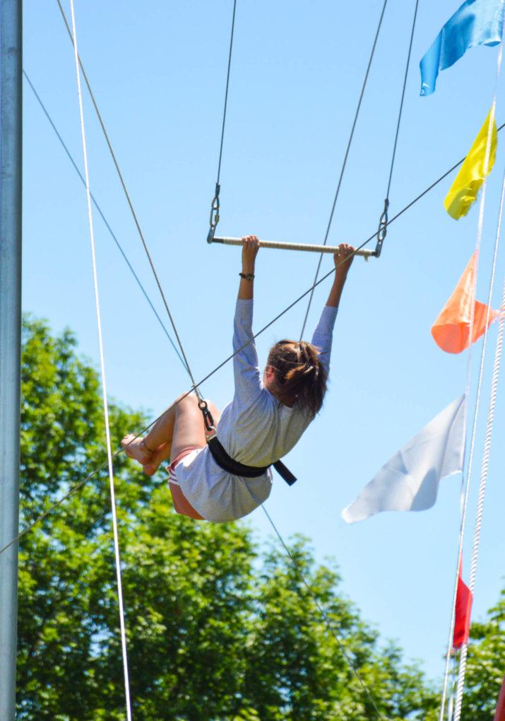 Camper swinging on a trapeze swing
