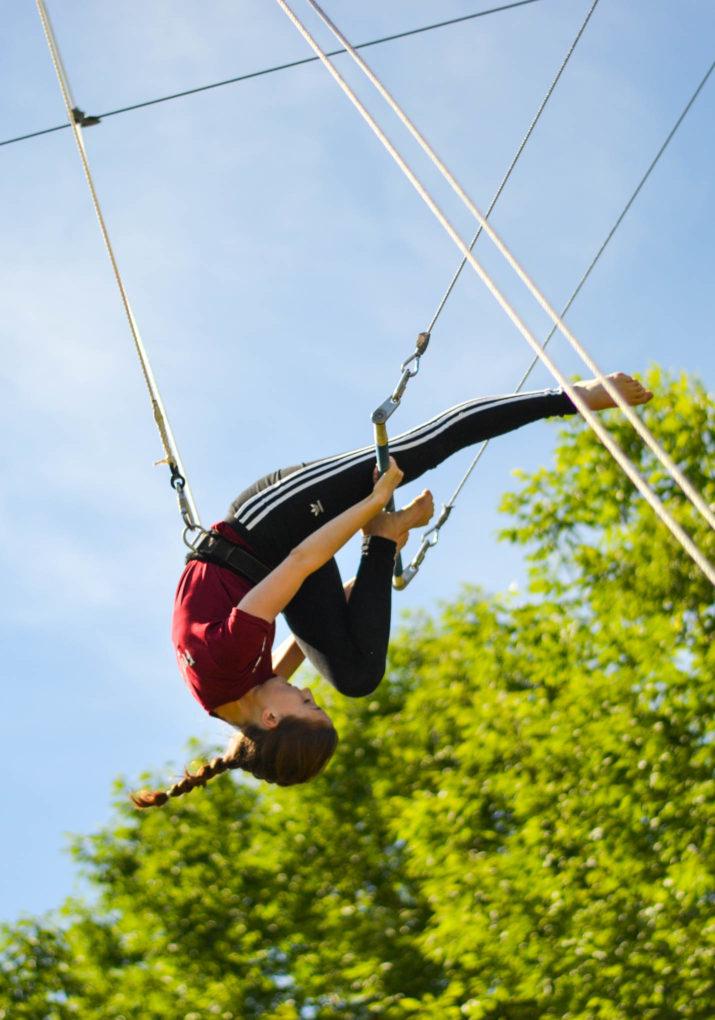 Camper doing a trapeze stunt