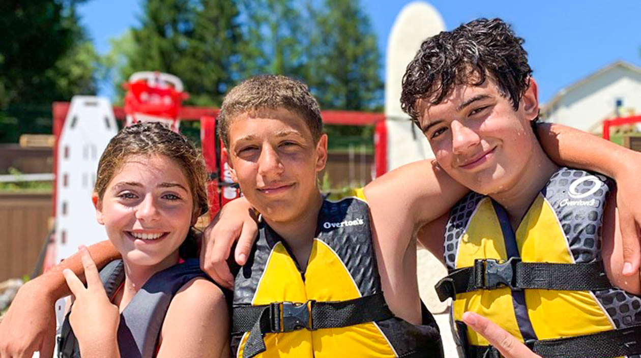 Three campers smiling wearing life vests by the dock