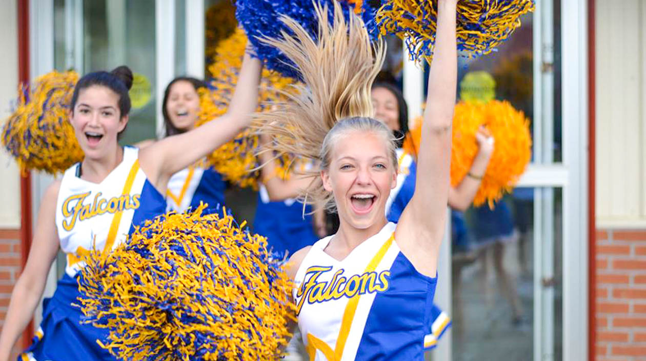 Cheerleaders smiling and jumping around