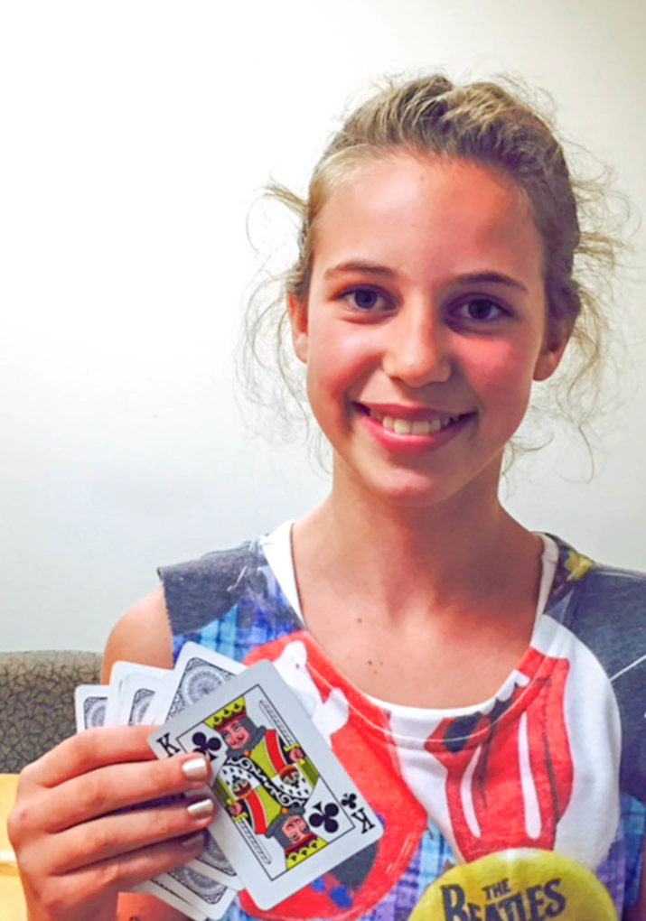 Girl holding up playing cards