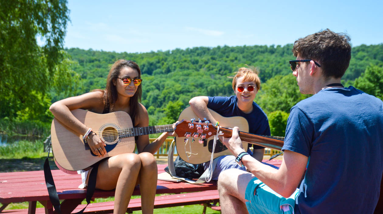 Campers having a guitar lesson outside