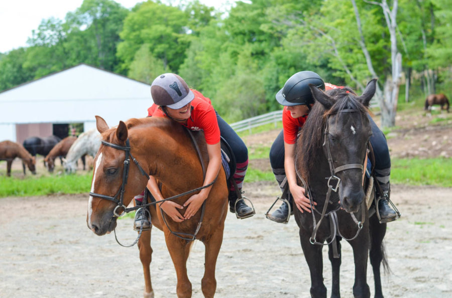 Two campers on horses bending over hugging their horses necks