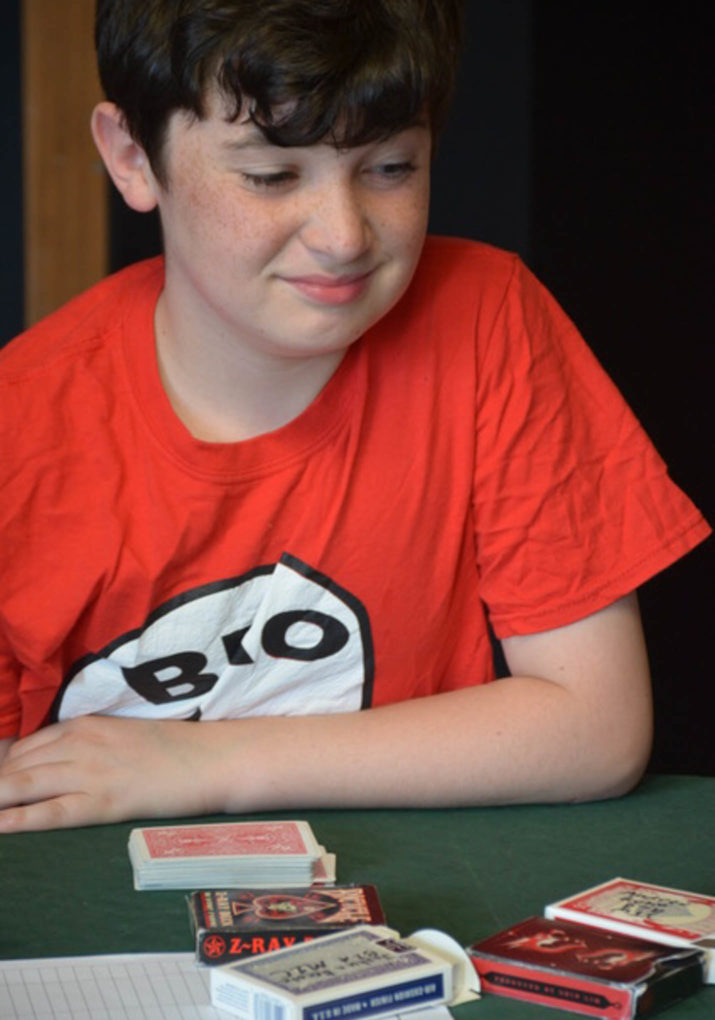 Boy sitting at a table with a deck of cards