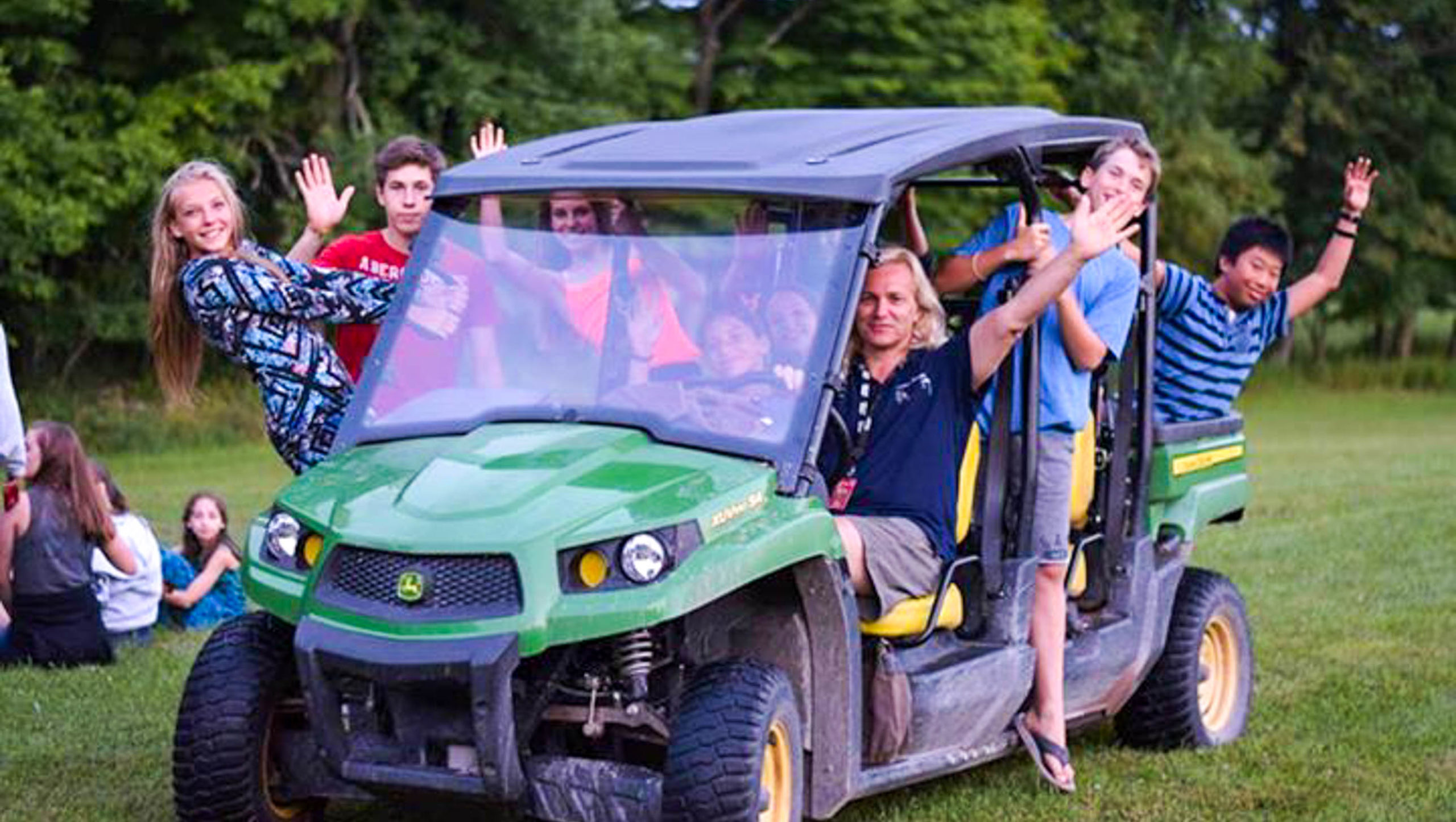 Director Nigel driving a golf cart with a bunch of campers