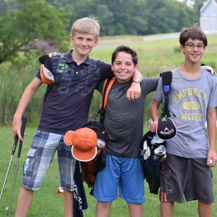 kids playing golf smiling at camera.