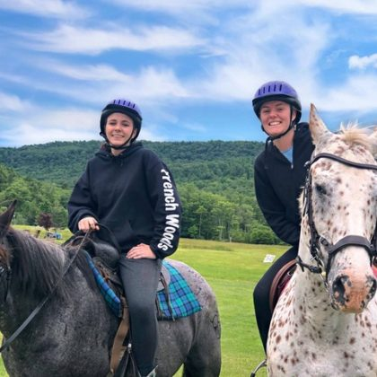 girls horseback riding smiling at camera.